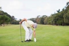 Mûrissez l'homme tenant le club de golf tout en se pliant Images libres de droits