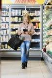 Mûrissez la femme à l'aide de la Tablette de Digital tout en marchant dans le supermarché photo libre de droits