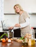 Mûrissez la femme au foyer à l'aide de l'ordinateur portable tout en faisant cuire la soupe Image stock