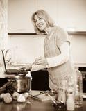Mûrissez la femme au foyer à l'aide de l'ordinateur portable tout en faisant cuire la soupe Photo stock