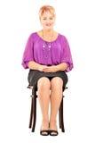 Mûrissez la femme de sourire s'asseyant sur une chaise en bois photographie stock