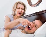 Mûrissez la fille fatiguée épuisée regardant l'ami de ronflement Image stock