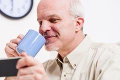 Mûrissez la lecture de sourire d'homme sur son écran de smartphone Image stock
