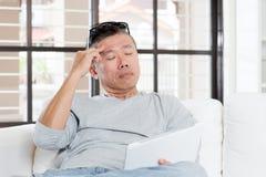 Mûrissez le mal de tête asiatique d'homme tout en à l'aide de la tablette Images stock