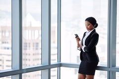 Mûrissez le service de mini-messages noir de femme d'affaires tout en se tenant image libre de droits