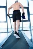 Mûrissez le sportif sans chemise s'exerçant sur le tapis roulant dans le gymnase Images libres de droits