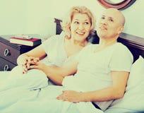Mûrissez les couples affectueux lounging dans le lit après avoir réveillé la caresse photographie stock libre de droits