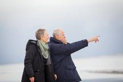 Mûrissez les couples heureux marchant sur la plage en automne photos stock