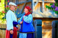Mûrissez les couples ukrainiens dans des costumes traditionnels parlant dans le village Image libre de droits