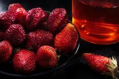 Mûrissez les fraises rouges dans un plat noir dans la perspective d'un verre avec le thé Images libres de droits