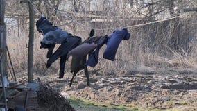 M?rk linne torkas p? ett rep i vinden i byn arkivfilmer