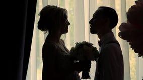 M?rka ?versikter av bruden och brudgummen mitt emot f?nstret flickan och den unga grabben st?r fr?n sidan och att v?nda mot varje lager videofilmer