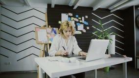 M?rkes- arbete f?r kvinna p? en b?rbar dator med en diagramminnestavla lager videofilmer