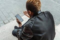 M?rkhyad man som ser mobiltelefonsk?rmen och sitter p? konkreta moment arkivfoton