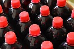 M?rkt - r?d fruktsirap i plast- flaskor royaltyfri fotografi