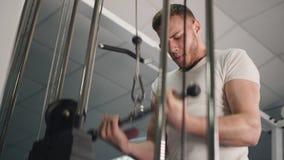M?sculos de entrenamiento masculinos del tr?ceps de los brazos usando la m?quina del cable para la masa del cuerpo Hombre en el g metrajes