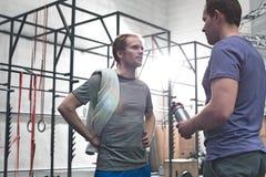 Męscy przyjaciele opowiada w crossfit gym Fotografia Stock