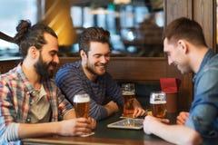 Męscy przyjaciele pije piwo przy barem z pastylka komputerem osobistym Zdjęcie Stock