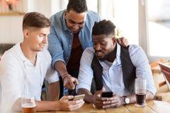 Męscy przyjaciele pije piwo przy barem z smartphone Zdjęcia Stock