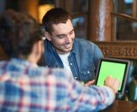 Męscy przyjaciele z pastylka komputerem osobistym przy barem Zdjęcia Stock