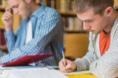 Męscy ucznie pisze notatkach przy bibliotecznym biurkiem Fotografia Royalty Free