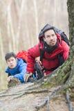 Męscy wycieczkowicze trekking w lesie Zdjęcia Royalty Free