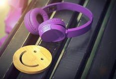 M?sica fina para el humor perfecto Auriculares inal?mbricos de la mentira p?rpura del color en un banco de madera oscuro Una sonr imagenes de archivo