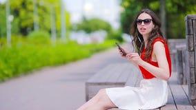 M?sica que escucha de la muchacha hermosa por smartphone el vacaciones de verano Turista atractivo joven con el tel?fono m?vil al almacen de video