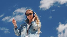 m?sica que escucha de la mujer joven con los auriculares al aire libre almacen de video
