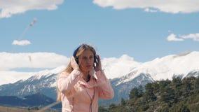 m?sica que escucha de la mujer joven con los auriculares al aire libre almacen de metraje de vídeo