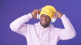 M?sica que escucha sorprendida feliz del hombre del inconformista con los auriculares en el estudio de la m?sica almacen de metraje de vídeo