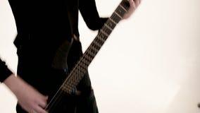 M?sico de sexo masculino joven en ropa negra con una guitarra baja negra en un fondo blanco M?sica expresiva baja del guitarrista metrajes