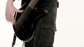 M?sico de sexo masculino joven en ropa negra con una guitarra baja negra en un fondo blanco M?sica expresiva baja del guitarrista almacen de video