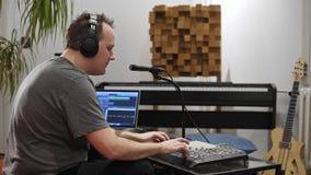 M?sico que canta y que juega el teclado de Midi en el estudio casero de la m?sica almacen de metraje de vídeo