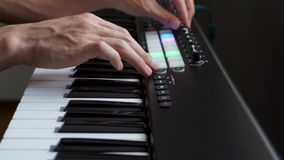 M?sico que joga o sintetizador do teclado de MIDI/controlador de MIDI no est?dio filme