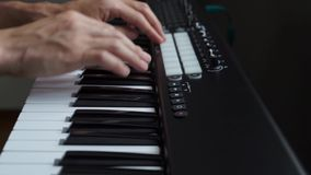 M?sico que joga o sintetizador do teclado de MIDI/controlador de MIDI no est?dio video estoque