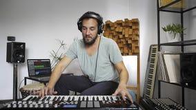 M?sico que juega el teclado de Midi en el estudio casero de la m?sica
