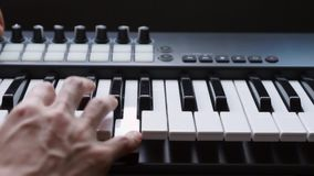 M?sico que juega el teclado de MIDI/el sintetizador del controlador midi en estudio metrajes