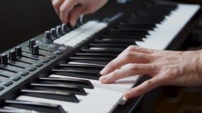 M?sico que juega el teclado de MIDI/el sintetizador del controlador midi en estudio
