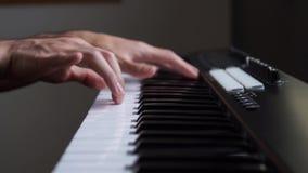 M?sico que juega el teclado de MIDI/el sintetizador del controlador midi en estudio almacen de metraje de vídeo