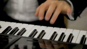 M?sico que juega en las llaves del piano del sintetizador del teclado almacen de video