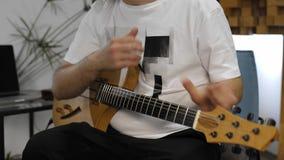 M?sico que tiene dolor de la mu?eca mientras que toca la guitarra el?ctrica en el estudio casero de la m?sica almacen de metraje de vídeo