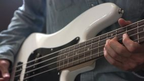 M?sico que toca la guitarra baja con la selecci?n en estudio almacen de metraje de vídeo