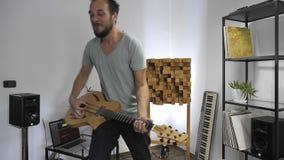 M?sico que toca la guitarra el?ctrica en el estudio casero de la m?sica almacen de metraje de vídeo
