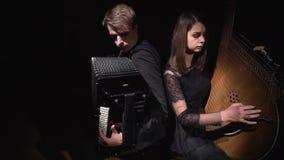 M?sicos muchacha y muchacho en un cuarto oscuro que juega en el acorde?n y el bandura almacen de video