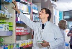 Męska farmaceuta pozuje w aptece Obrazy Royalty Free