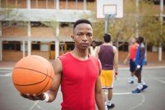 Męska gracza koszykówki mienia koszykówka w boisko do koszykówki Obraz Stock