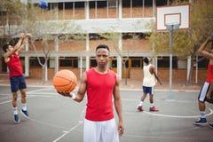 Męska gracza koszykówki mienia koszykówka w boisko do koszykówki Zdjęcia Stock