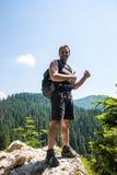 Męska wycieczkowicz pozycja na prawdziwej wysokiej falezie Zdjęcie Stock