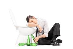 Męski alkoholiczny dosypianie na toalecie Zdjęcia Royalty Free